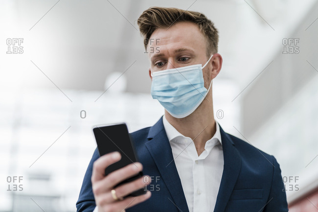 Businessman using mobile phone while wearing face mask in city