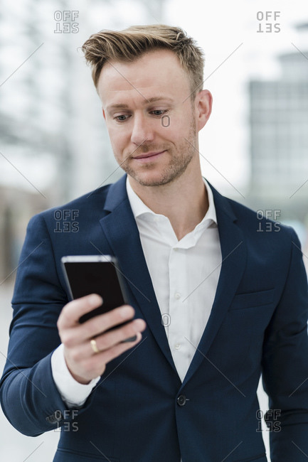 Confident businessman texting through mobile phone in city