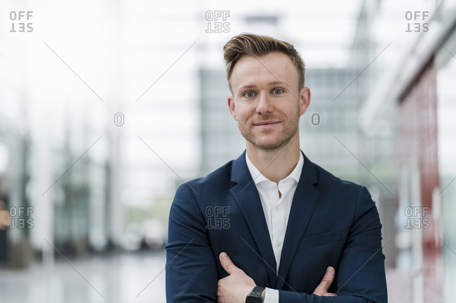 Smiling businessman with arms crossed standing in city