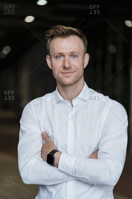 Confident businessman with arms crossed standing in city