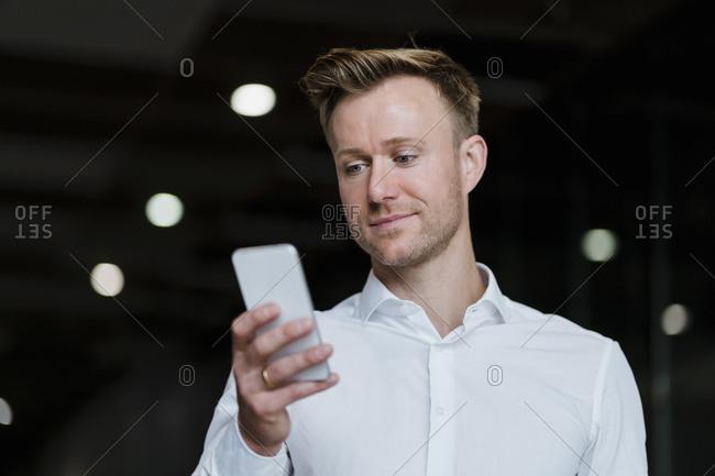 Confident businessman texting through smart phone in city