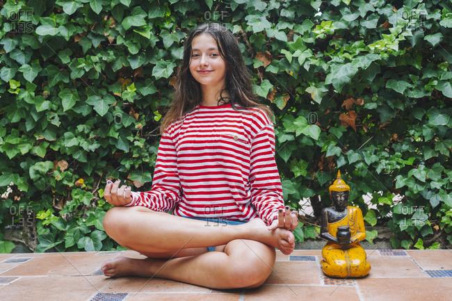 Smiling girl meditating by Buddha sculpture in backyard