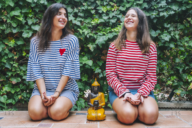 Smiling sisters meditating with Buddha sculpture in backyard