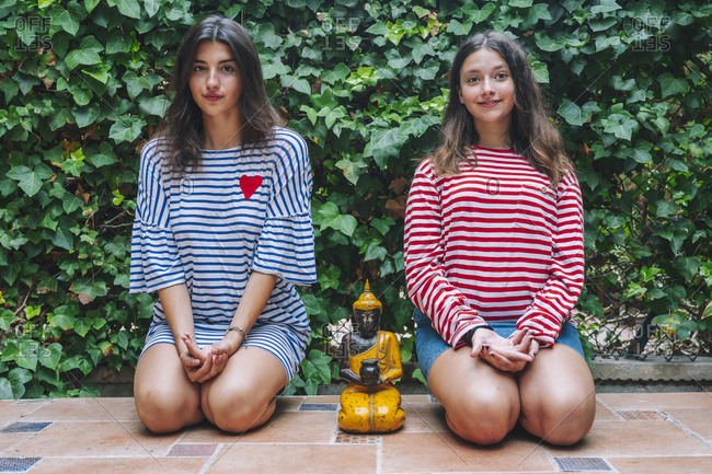 Sisters doing meditation with Buddha sculpture in backyard