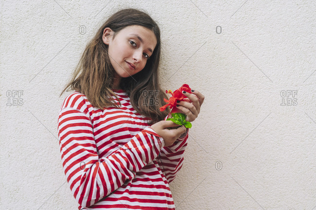 Girl holding hibiscus flower while standing against wall