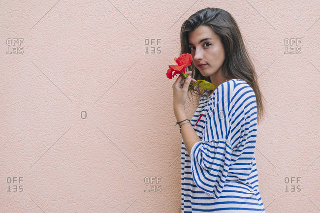 Beautiful young woman holding hibiscus flower while standing against wall