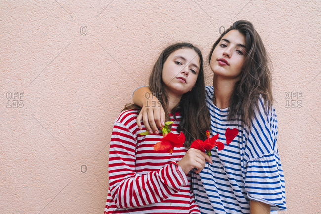 Sisters holding hibiscus flowers while standing against wall