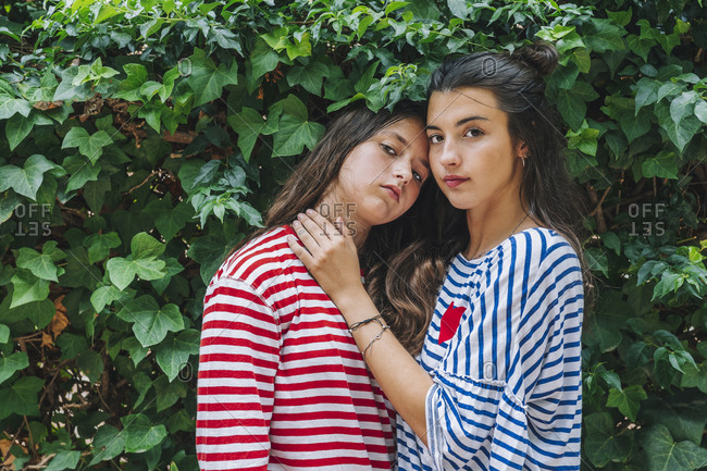 Sisters in striped casuals standing against plants in backyard