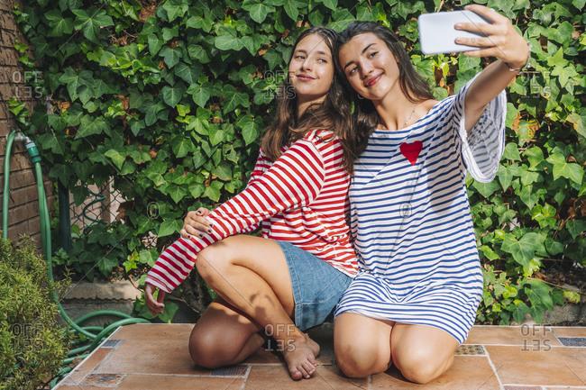 Smiling sisters while taking selfie on smart phone while kneeling in backyard