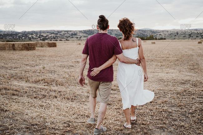 Couple with arm around walking in field during sunset