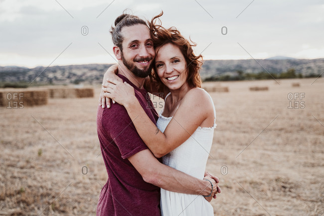 Smiling couple with arm around standing in field during sunset