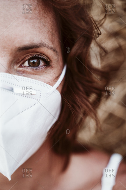 Close-up of woman wearing face mask against hay during pandemic