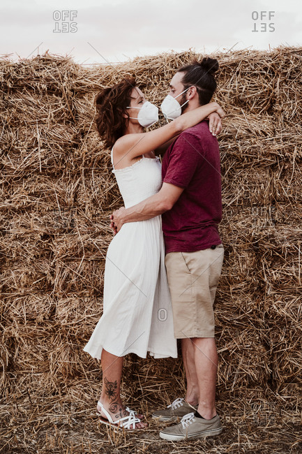 Man and woman wearing face mask with arm around standing in field during COVID-19