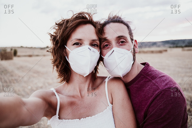 Man and woman wearing face mask standing in field during COVID-19