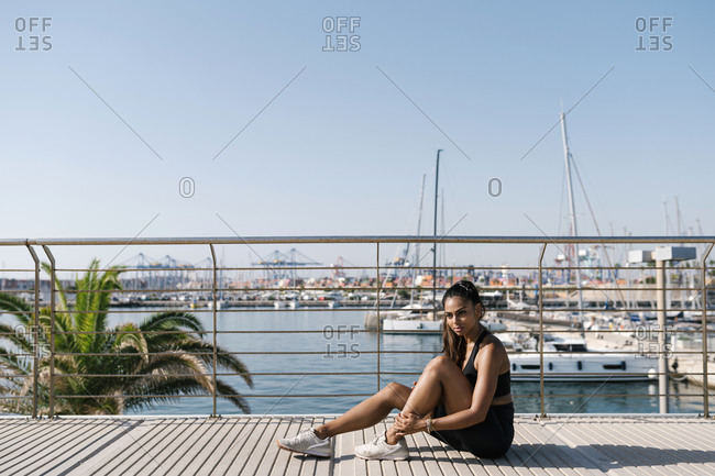 Woman sitting on boardwalk in sports clothing during sunny day