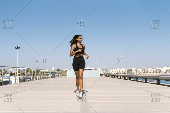Woman jogging at harbor against clear sky during sunny day