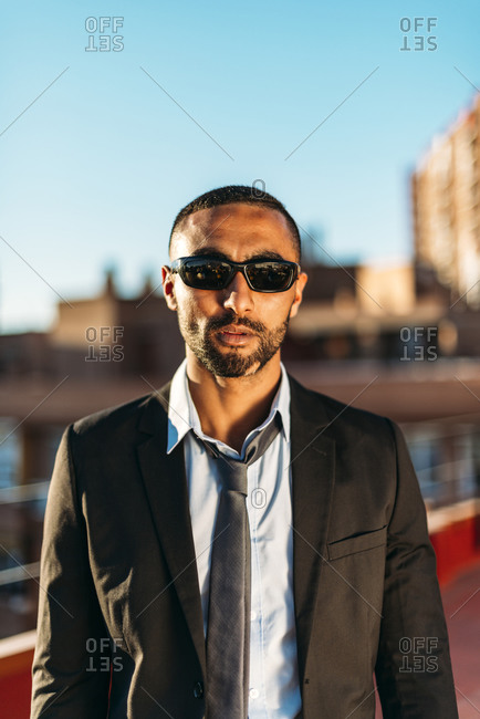 Confident businessman wearing sunglasses while standing at rooftop