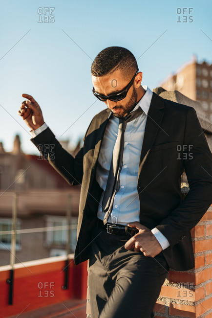 Businessman wearing sunglasses while standing at rooftop