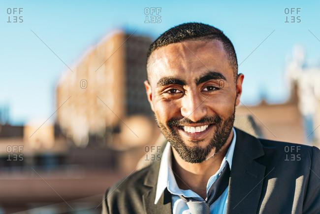 Handsome male entrepreneur smiling at rooftop