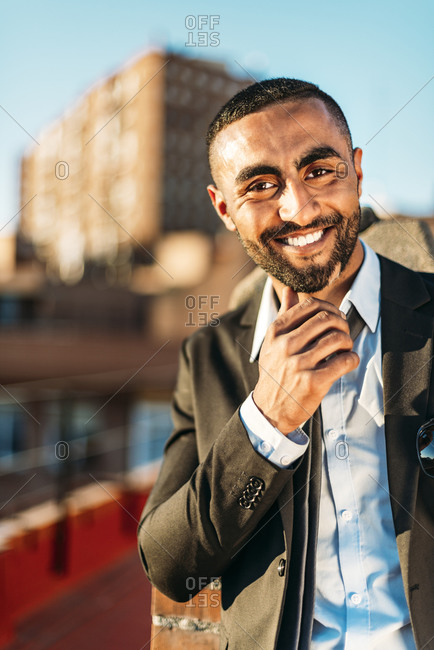 Smiling businessman standing at rooftop in city