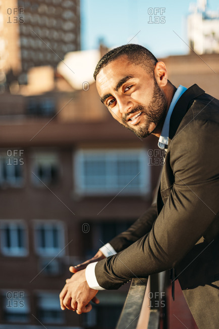 Young male professional leaning on railing at rooftop in city