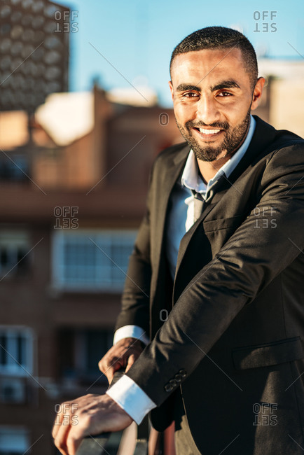 Businessman standing by railing on rooftop in city