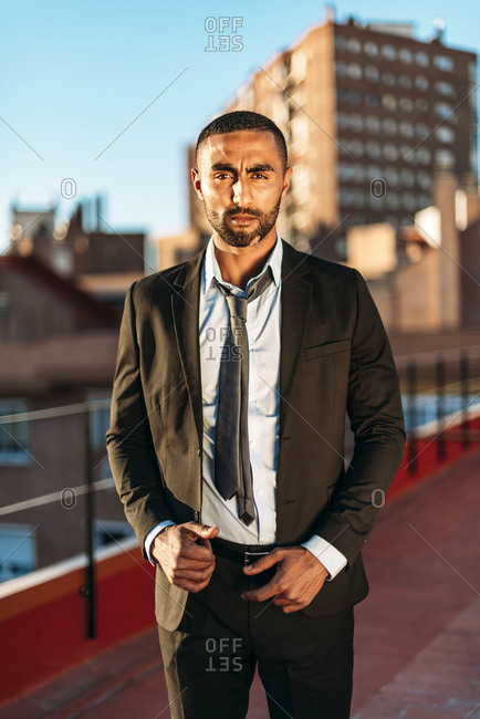 Well-dressed young male entrepreneur standing on rooftop in city