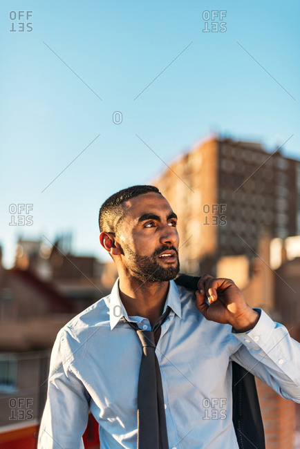 Male professional holding suit on shoulder while looking away on rooftop in city