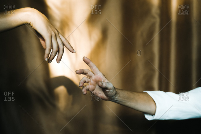 Hands of mother and daughter reaching against curtain