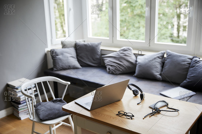 Laptop on table by furniture in living room at home