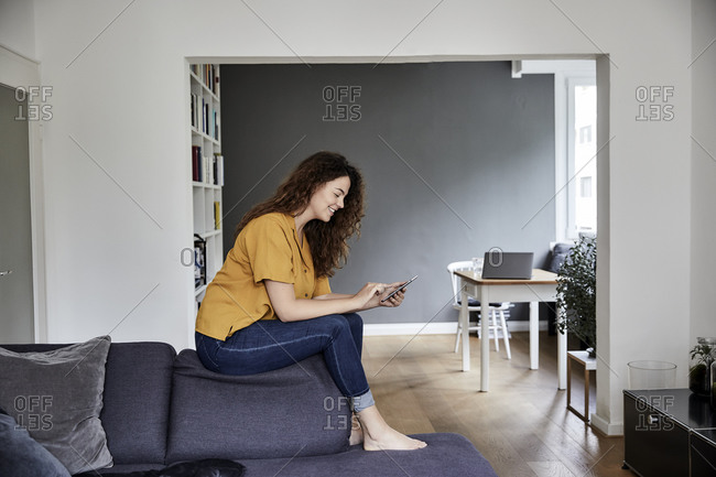 Woman using mobile phone while sitting on top of sofa at home