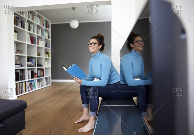 Smiling female student holding book and looking away while sitting by television set at home