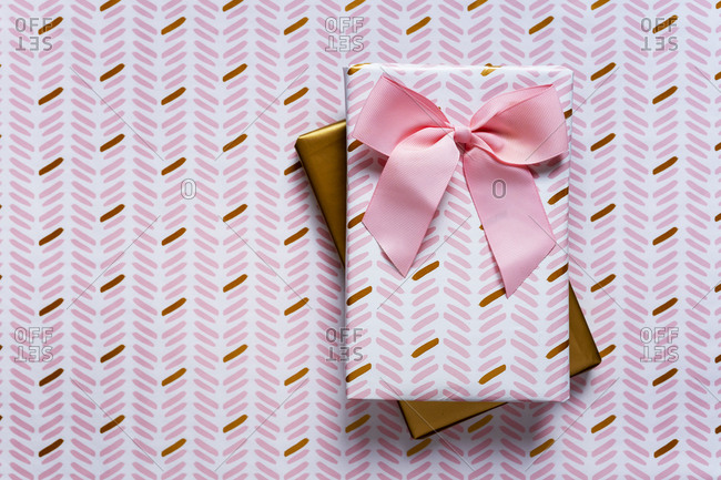 Two wrapped gifts against wrapping paper background