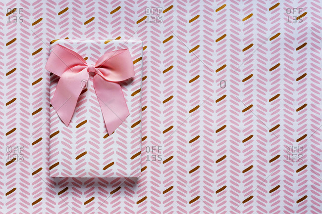 Pink wrapped gift against wrapping paper background