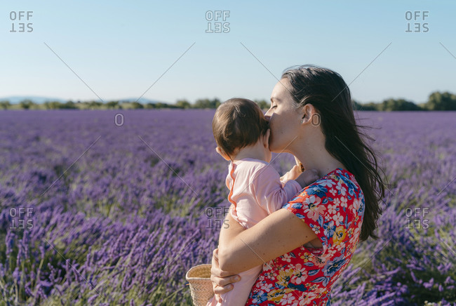 Woman standing in vast lavender field with baby girl in hands