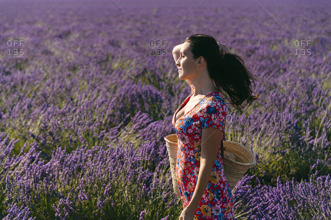 Portrait of beautiful woman standing in vast lavender field with hand in hair