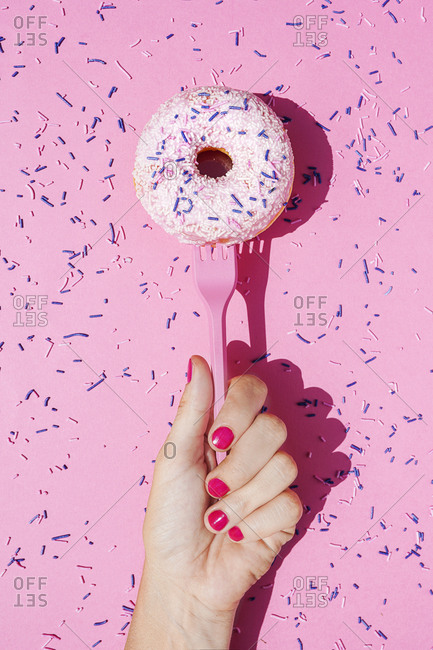 Hand of woman holding fork with sweet doughnut covered in sugar sprinkles