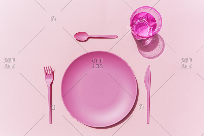 Studio shot of pink plastic plate- plastic cutlery and glass of water