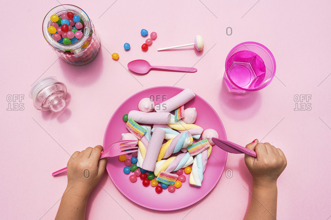Hands of baby girl preparing to eat plate filled with various sweets