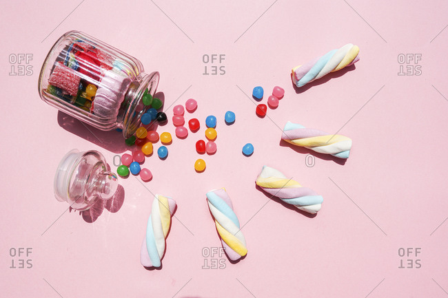 Studio shot of twisted marshmallows and candies spilling out from toppled jar