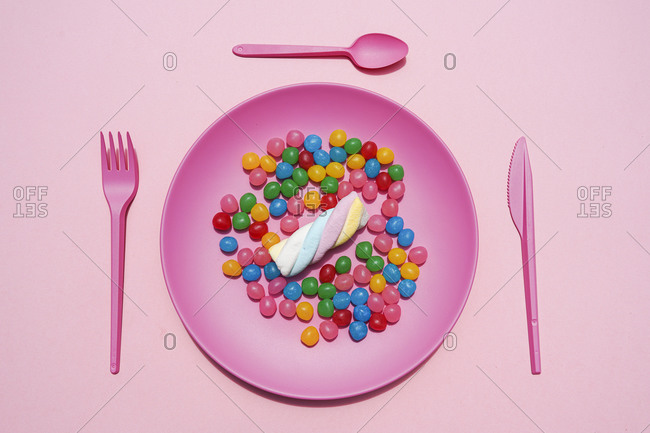 Studio shot of plastic plate full of candies and single marshmallow