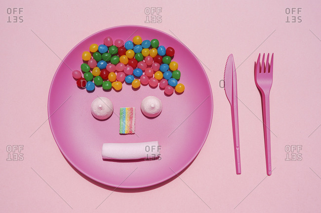 Studio shot of plastic plate with colorful candies and anthropomorphic face made of marshmallows and gum drop