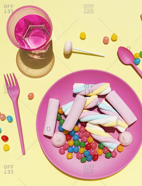 Studio shot of glass of water and plastic plate filled with various sweets