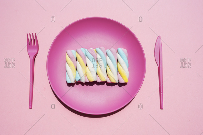 Studio shot of plastic plate with row of twisted marshmallows