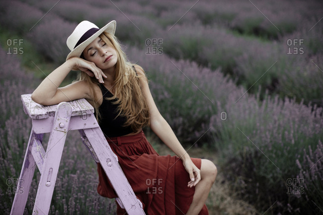 Woman sitting on ladder in lavender field