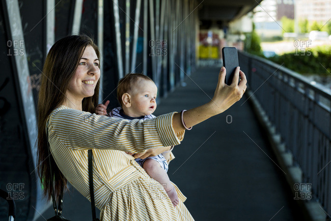 Smiling mother with her baby boy taking a selfie on bridge