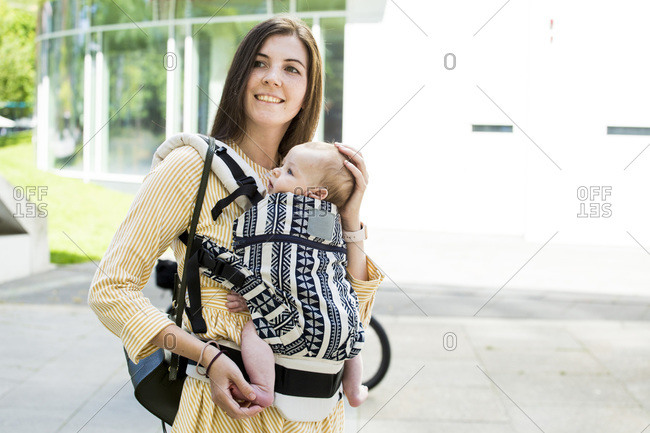 Smiling mother with her baby boy in baby carrier in city