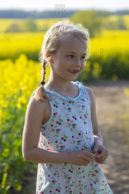 Cute little girl standing in farm of rapeseed field