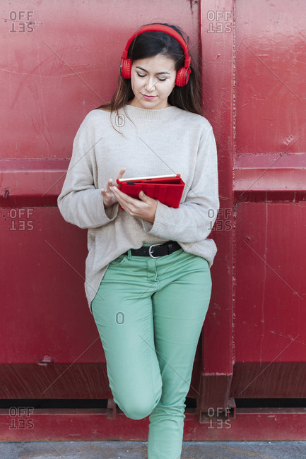 Trendy beautiful woman listening to songs while using digital tablet against red metallic wall