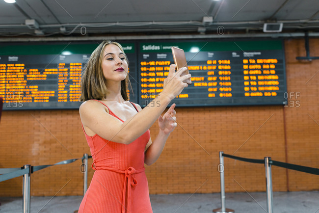 Beautiful young woman taking selfie while standing at railroad station